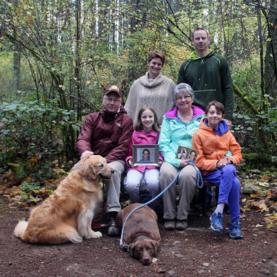 Family with two dogs on leashes pose for photo in the woods